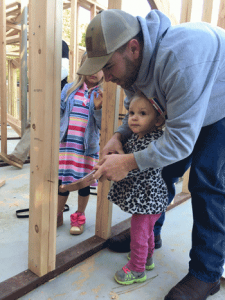 Johnathan helping his daughter hammer a nail into their home