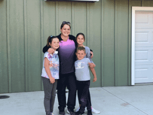 Alicia with her family and keys to their new home
