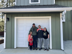 Johnathan and Kindra with their family and the keys to their home